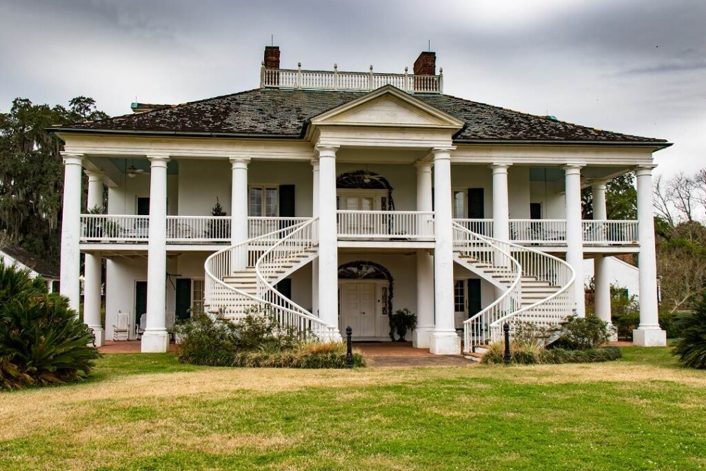 two story white house with large columns and a double sided staircase