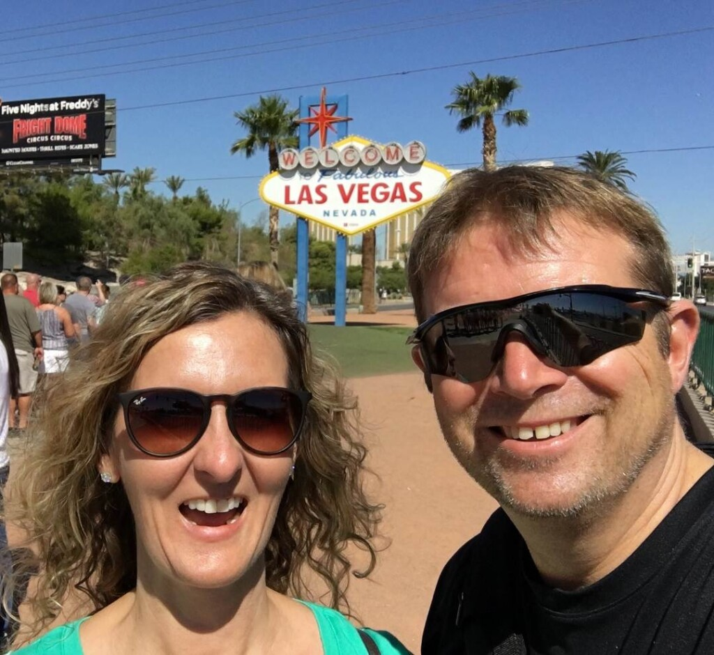 Girl with curly blonde hair wearing sunglasses and guy with blonde hair wearing sunglasses in front of the welcome to las vegas sign
