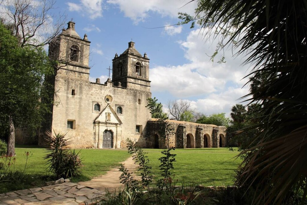 Old church with two bell towers and an arched walkway beside it