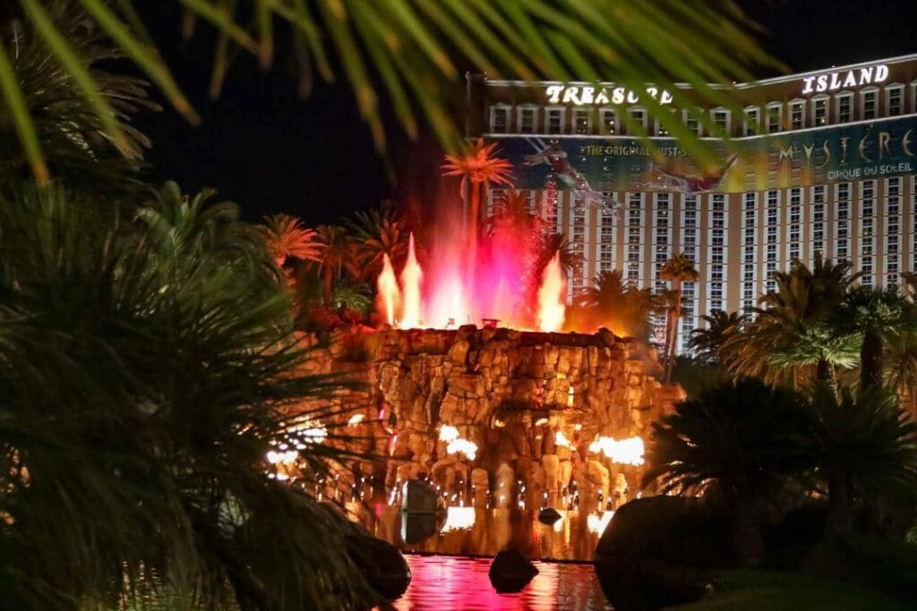red and white flames shooting out of the top of a man made rock volcano at the Mirage Hotel in Las Vegas