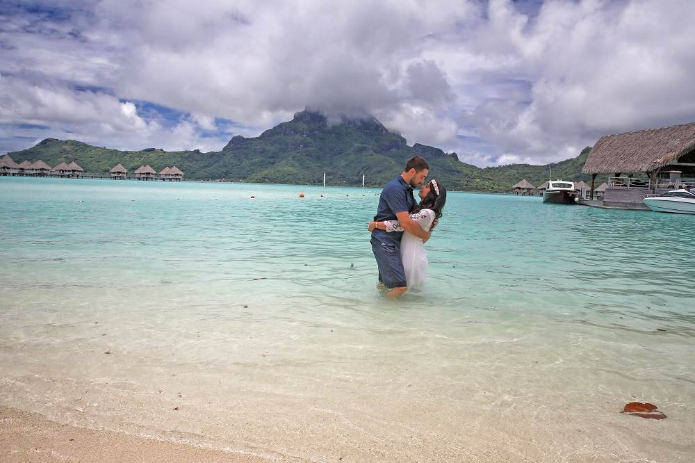 turquoise water of the ocean with a mountain in the back and a couple embracing one another
