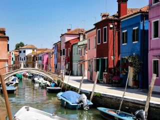 Colorful houses line a canal with boats in it