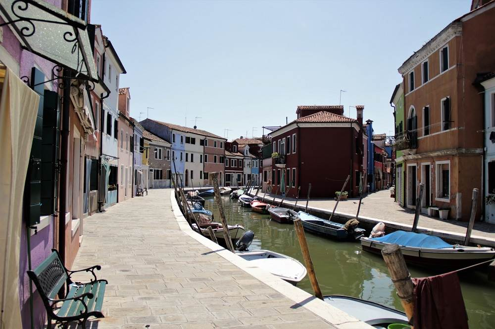 Colorful houses lining a canal with boats