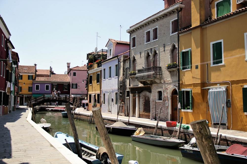 Colorful houses line a canal with boats docked
