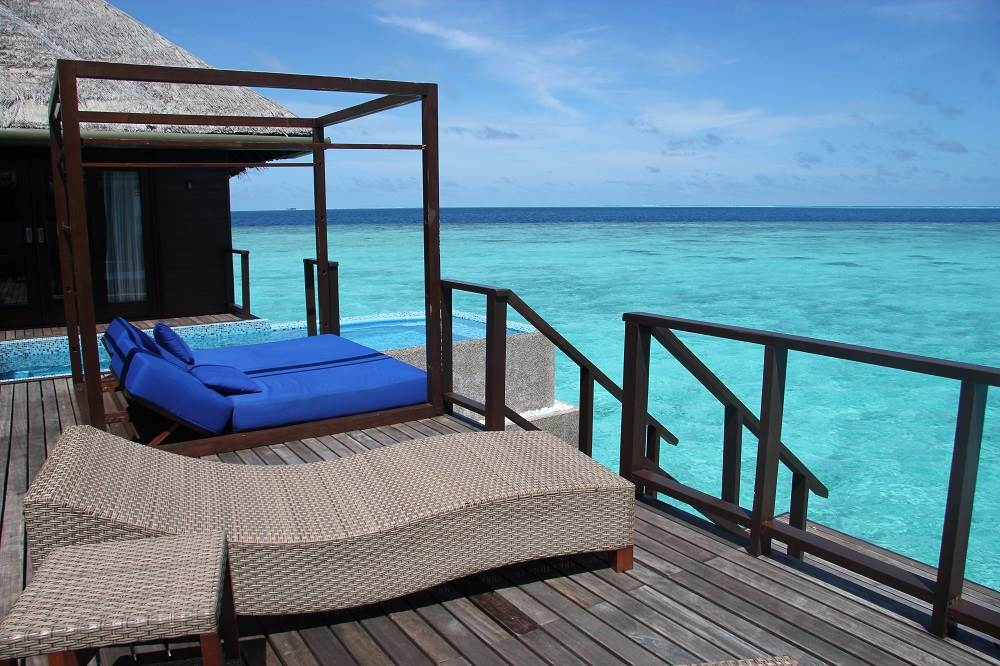 wooden deck with chaise lounge chairs overlooking turquoise blue water