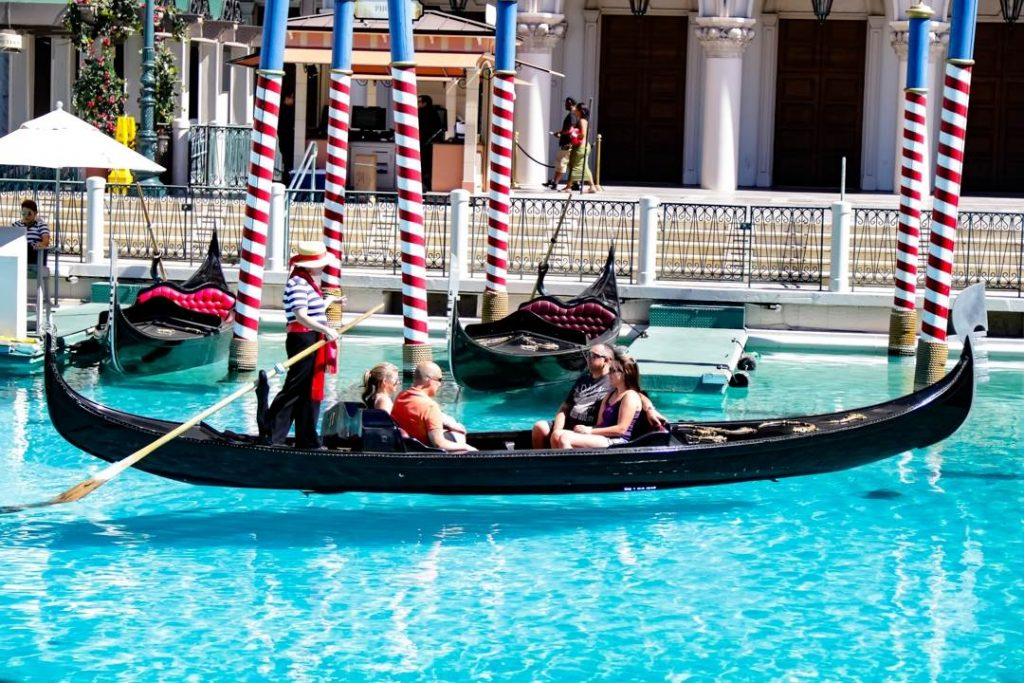 gondola in a canal with a gondonlier and four passengers