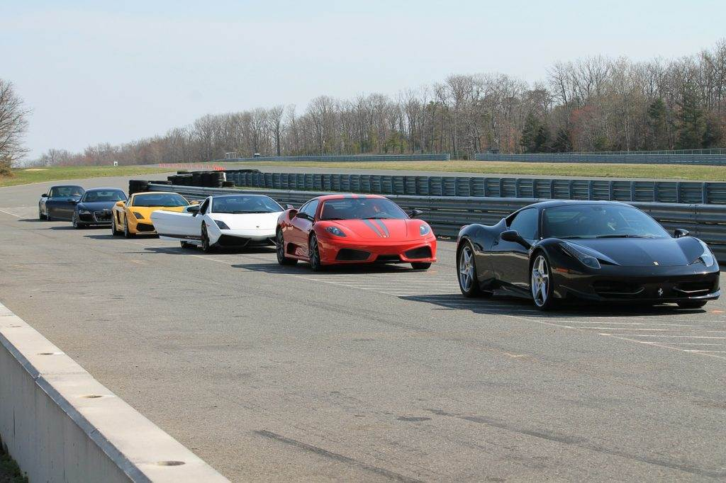several exotic cars in a row on a track