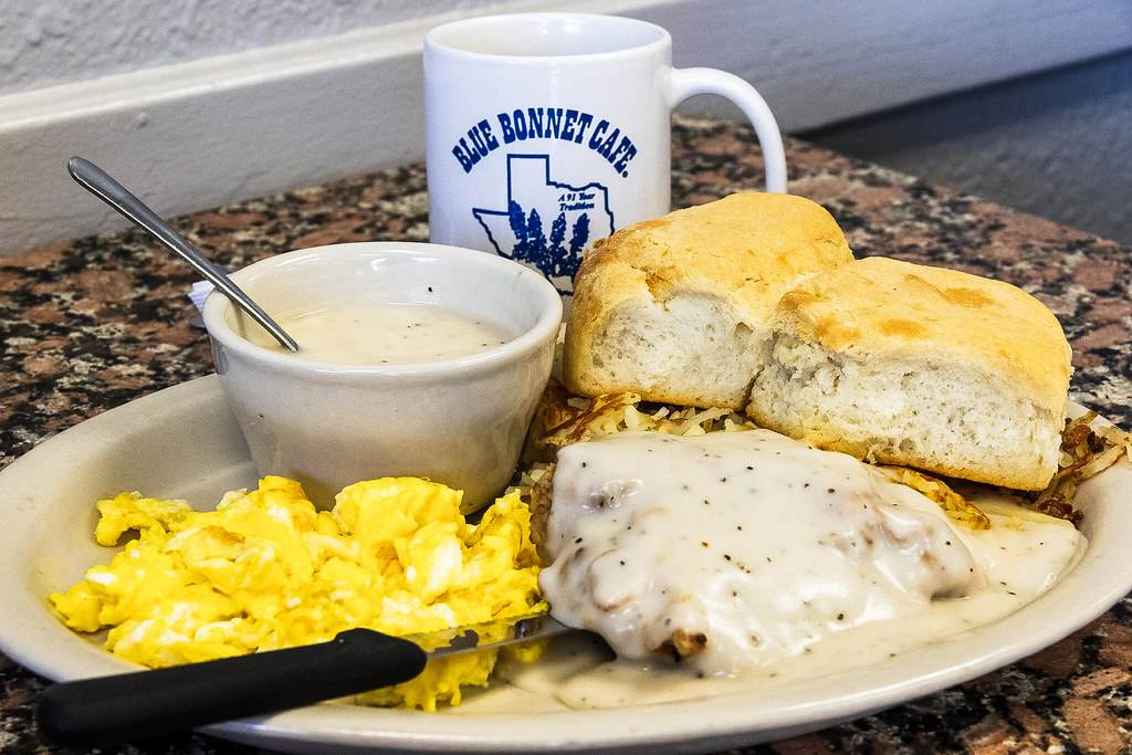 breakfast plate with biscuits, eggs gravy and hashbrowns