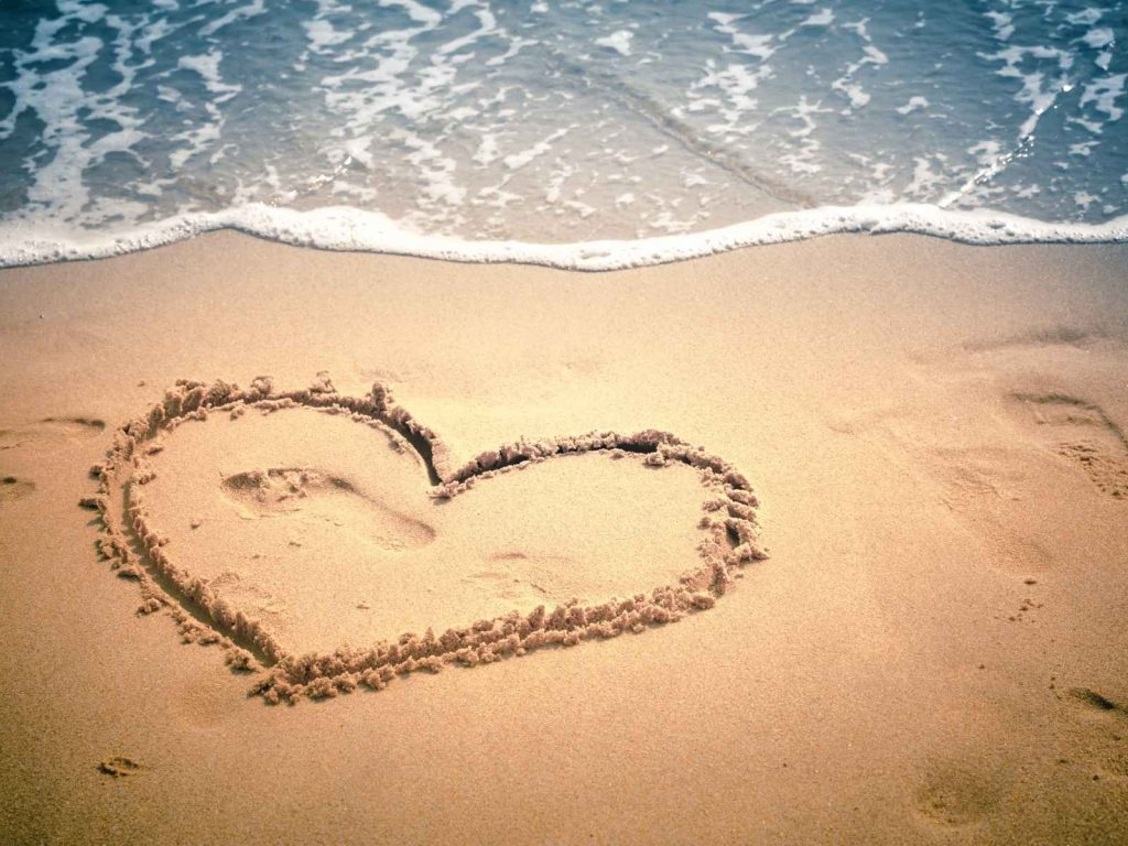 beach with a heart drawn in the sand