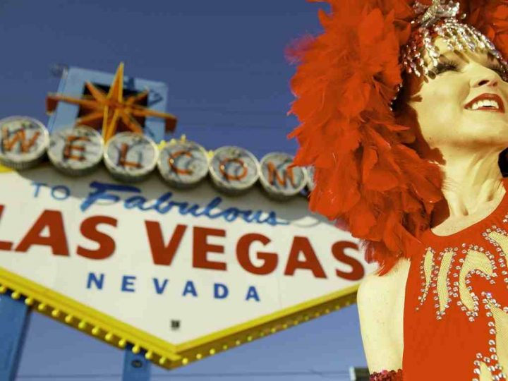 Vegas showgirl in front of the welcome to Las Vegas sign