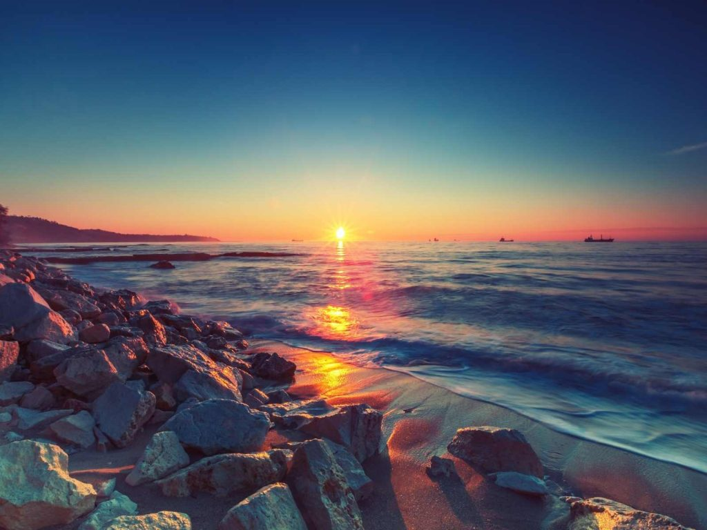sunset over the ocean with rocks on the beach