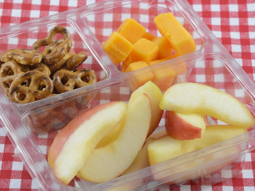 snack tray with apple slices, cheese cubes, and pretzel twists
