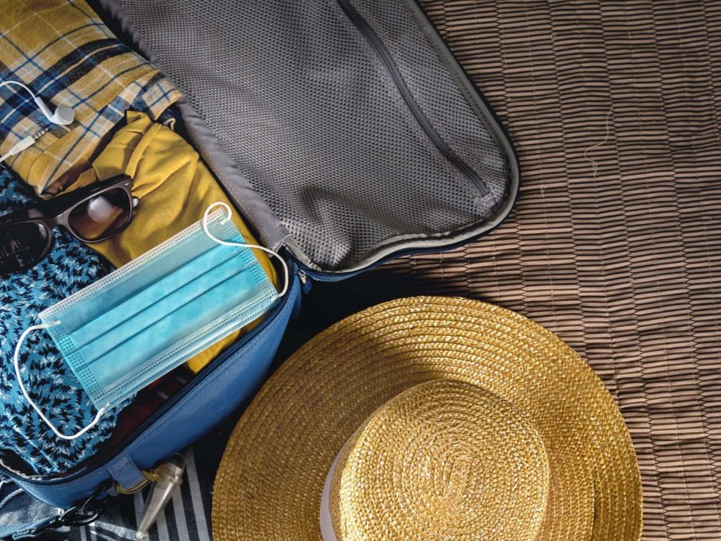 open suitcase with clothes in it and a hat beside it