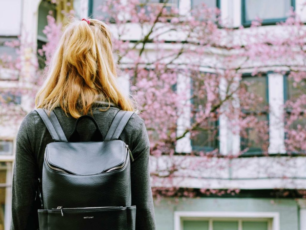 girl wearing backpack with back to camera and trees in the background