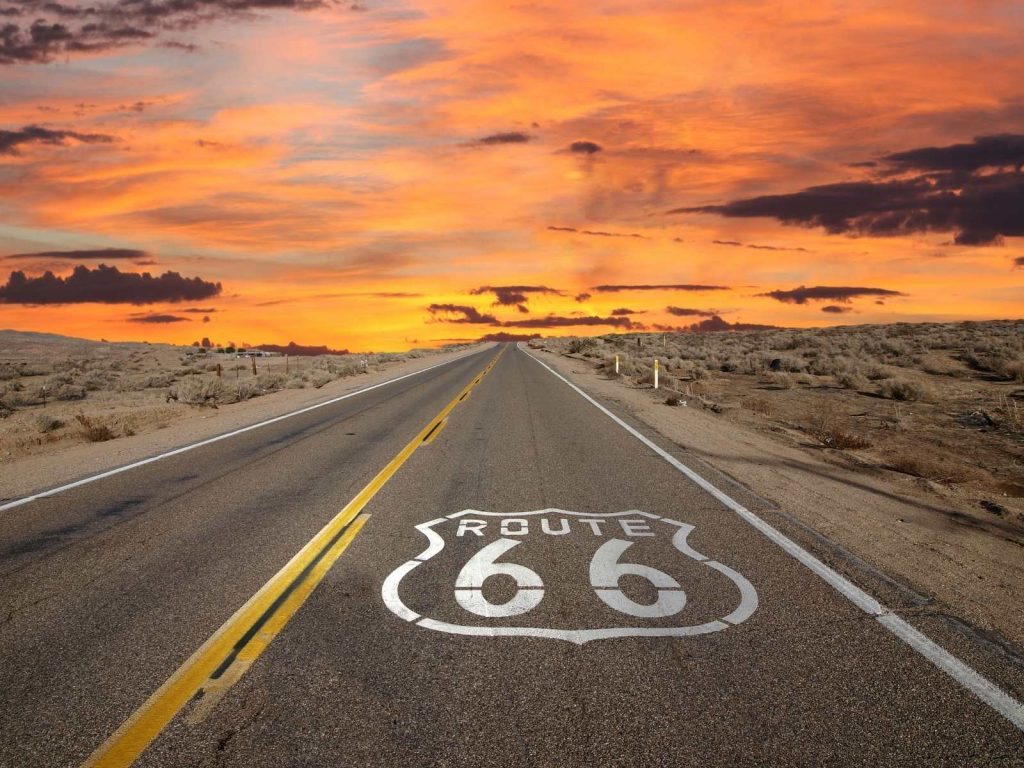 road with route 66 painted on it and sunset in the distance